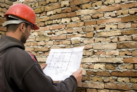 young male builder holding engineer project in front of brick wall Stok Fotoğraf