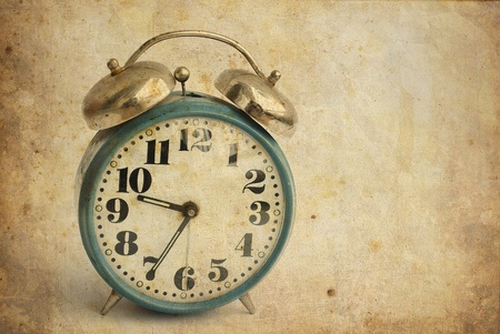 clock hands: old and rusty alarm clock isolated on vintage background Stock Photo
