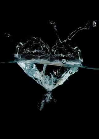 blue water shaped as a heart on black background photo