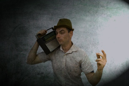 retro man listening to old radio on vintage background