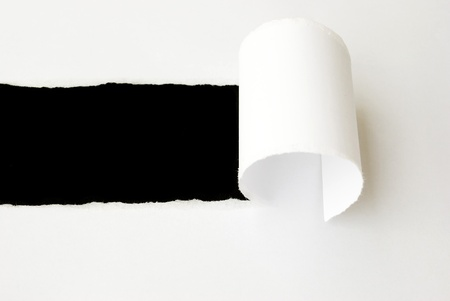torn white sheet of paper with black background and copyspace