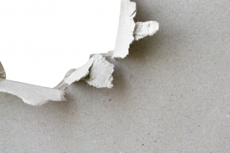 torn hole in sheet of paper with white background and copyspace photo
