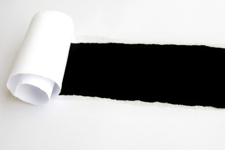 tear: torn white sheet of paper with black background and copyspace