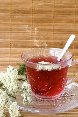 Achillea millefolium tea on wooden mat with fresh herbs photo