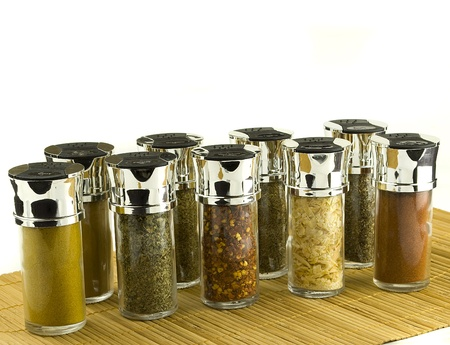 different spices in glass jars on wooden mat Stock Photo - 12606459