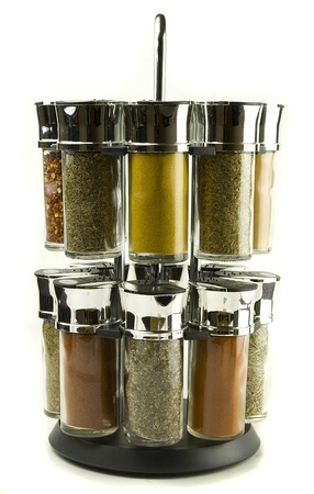 different spices rolling set in glass jars on wooden mat photo