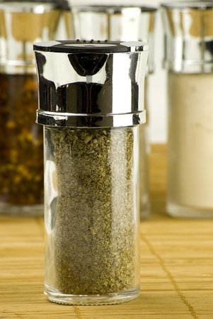 marjoram: dry marjoram leaves in a glass jar on different spices background over wooden mat