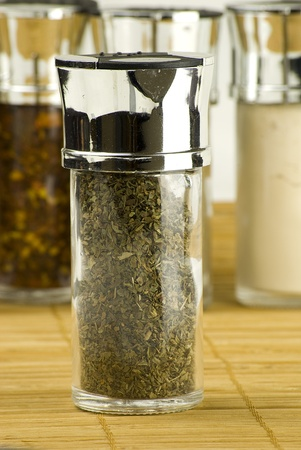 dried herbs: dry basil in a glass jar on different spices background over wooden mat