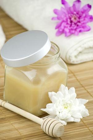 produits de beaut�: d�tente ar�me de lait d'amande de coco et la vanille mousse pour le bain au miel sur tapis bois