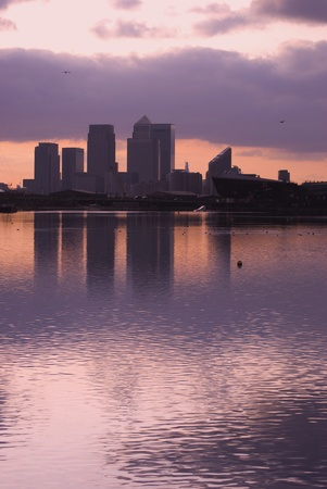 blue tone of canary wharf silhouette over canal at sunset photo