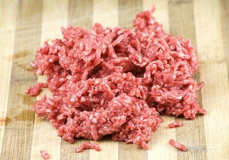carne picada: montón de carne cruda fresca picada sobre un tablero de madera de la cocina Foto de archivo