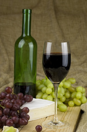 bottle and glass of red white grapes and brie cheese on brown background photo