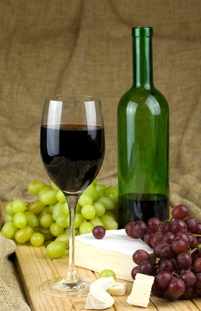 bottle and glass of red white grapes and brie cheese on brown background Stock Photo - 12989745