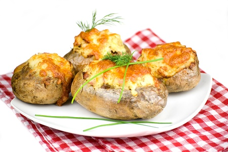 stuffed potatoes covered with cheddar cheese decorated with chives and dill leaves in a white plate Stock Photo - 12989743
