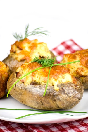 stuffed potatoes covered with cheddar cheese decorated with chives and dill leaves in a white plate Stock Photo - 12989731