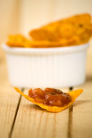 spicy tortilla chips and tomato salsa dip over wooden board Stock Photo - 12989732