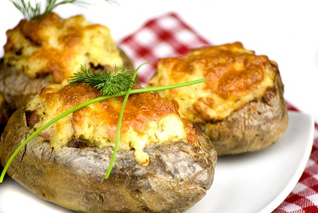baked potatoes: stuffed potatoes covered with cheddar cheese decorated with chives and dill leaves in a white plate