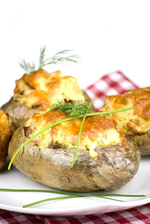 stuffed potatoes covered with cheddar cheese decorated with chives and dill leaves in a white plate photo