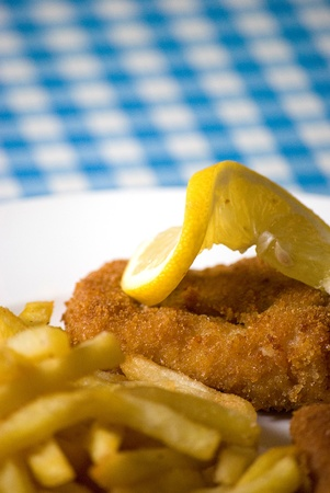 fish and chips in a plate over blue and white table photo