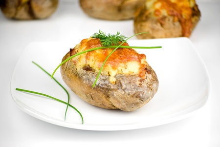 jacket potato: stuffed potatoes covered with cheddar cheese decorated with chives and dill leaves in a white plate