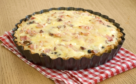 quiche with ham cheese salami muchrooms beans eggs in a tray photo