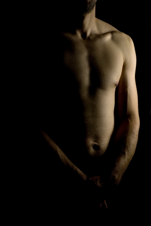 sexy fit naked male body on black background low key photo