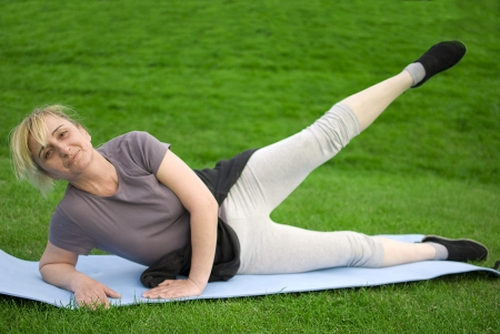 keeping fit: middle aged woman keeping fit with exercises in a park Stock Photo
