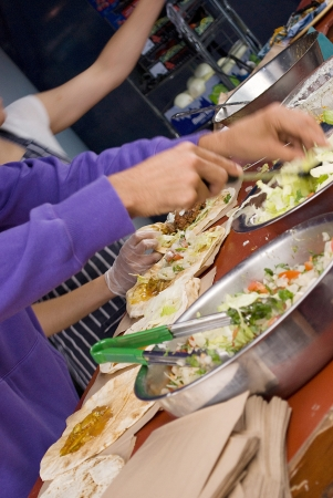 preparing beef wrap with fresh vegetables on a market photo