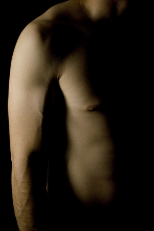 triceps: sexy fit male body on black background low key Stock Photo