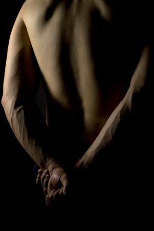 sexy fit male body on black background low key photo
