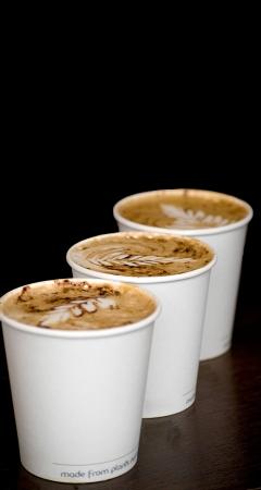 drie cappuccino kopjes over houten tafel Stockfoto