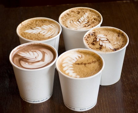 five cappuccino cups over wooden table