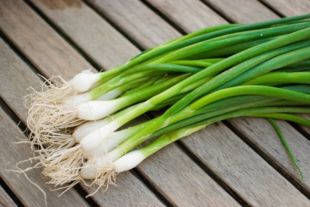 fresh green spring onions over old wooden table photo