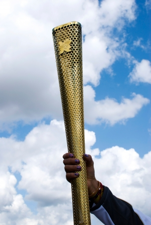 LONDON, UNITED KINGDOM-JULY 21: Olympic games volunteer holding the torch at Greenwich on July 21, 2012 in London, UK. The event is from July 27 to August 12, 2012.