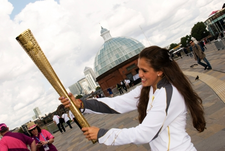 olympic symbol: LONDON, UNITED KINGDOM-JULY 21: Olympic games volunteer holding the torch at Greenwich on July 21, 2012 in London, UK. The event is from July 27 to August 12, 2012. Editorial