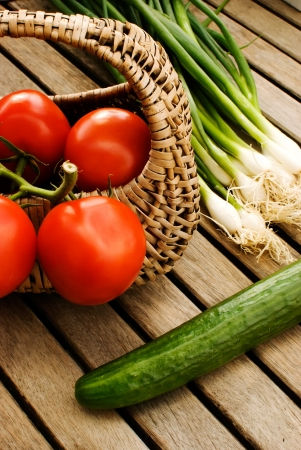 fresh vegetables tomatoes cucumber and green onion in basket over wooden table photo