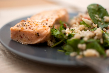 roasted salmon fillet with fresh green leaves salad and quinoa