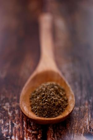 marjoram: marjoram spice in wooden spoon over wood background - selective focus