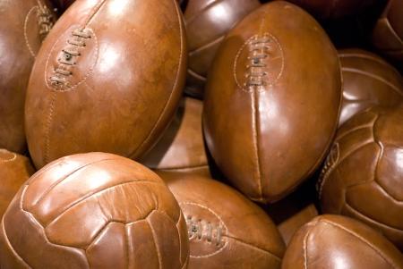 pelota de rugby: pila de viejos balones de cuero marrón de la vendimia Foto de archivo