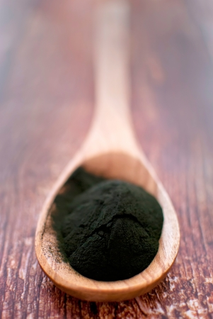 organic spirulina algae powder in wooden spoon photo