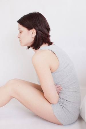 young woman with stomach pain sitting on floor holding holding her tummy photo
