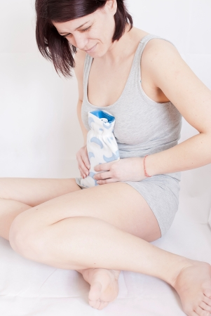 young woman with stomach pain sitting on floor holding hot water bottle Stock Photo - 18914119