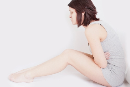 ovaries: young woman with stomach pain sitting on floor holding holding her tummy