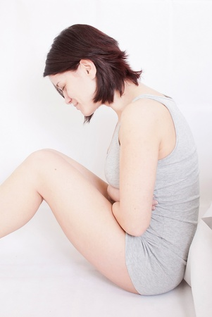 ovaries: young woman with stomach pain sitting on floor holding hot water bottle Stock Photo