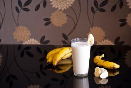 fruit drinks: fresh banana smoothie and fruits on black background