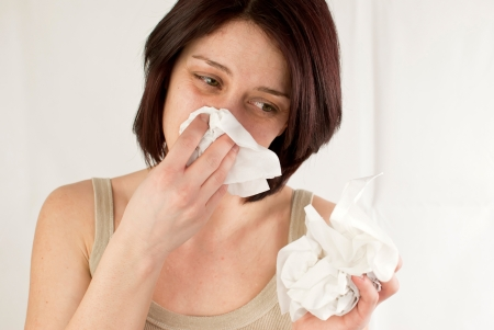 allergic reaction: sneezing woman holding tissues, allergy or cold flu concept Stock Photo