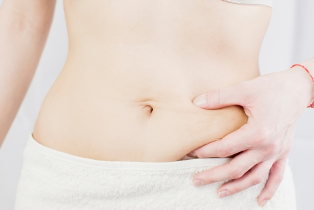 hands on waist: young woman holding her skin for cellulite check Stock Photo