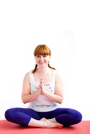 middle aged redhead woman exercising yoga isolated on white photo