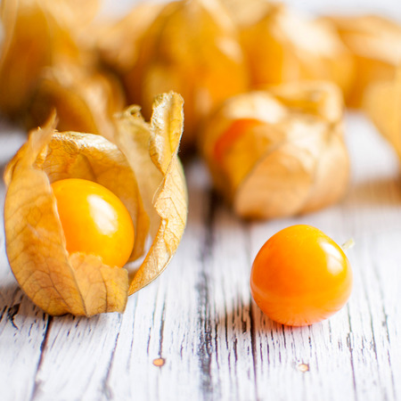 physalis: ripe healthy orange physalis over wooden board Stock Photo