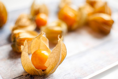 husk tomato: ripe healthy orange physalis over wooden board Stock Photo